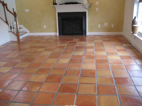 Exciting saltillo tile with white baseboard and fireplace